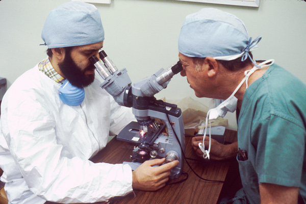 physicians looking into microscope